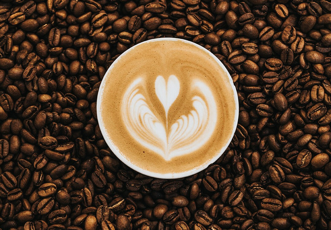 coffee beans surround cappuccino